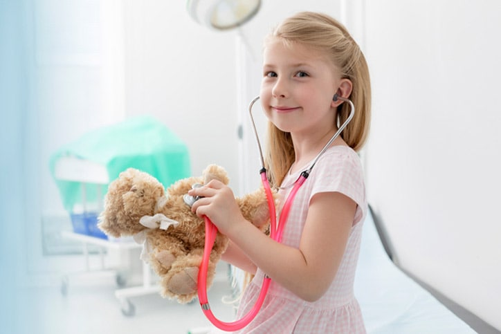 Portrait smiling girl using stethoscope on teddy bear in examination room