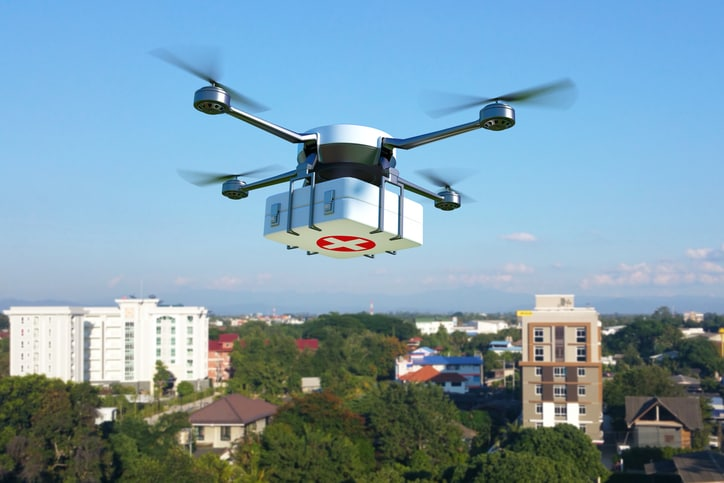 Drone with first aid kit flying over the town