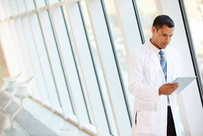Doctor reading FHI report on tablet